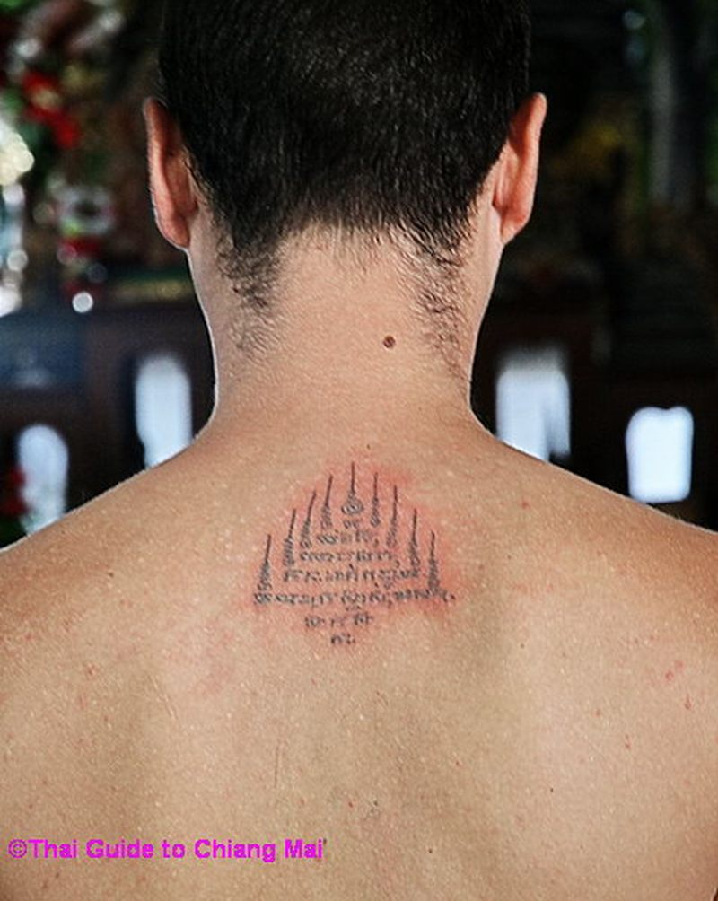 Small religious buddhist tattoo on upper back