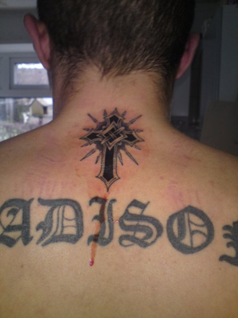 Small religious cross tattoo on neck back