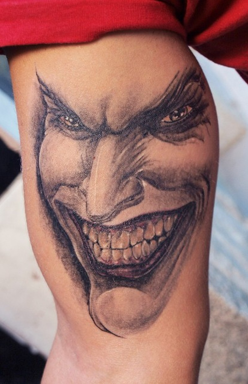 Smiling joker tattoo on muscles