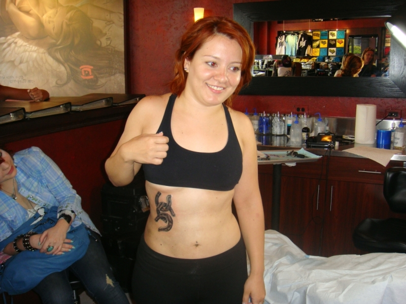 Smiling woman with horseshoes tattoo on stomach
