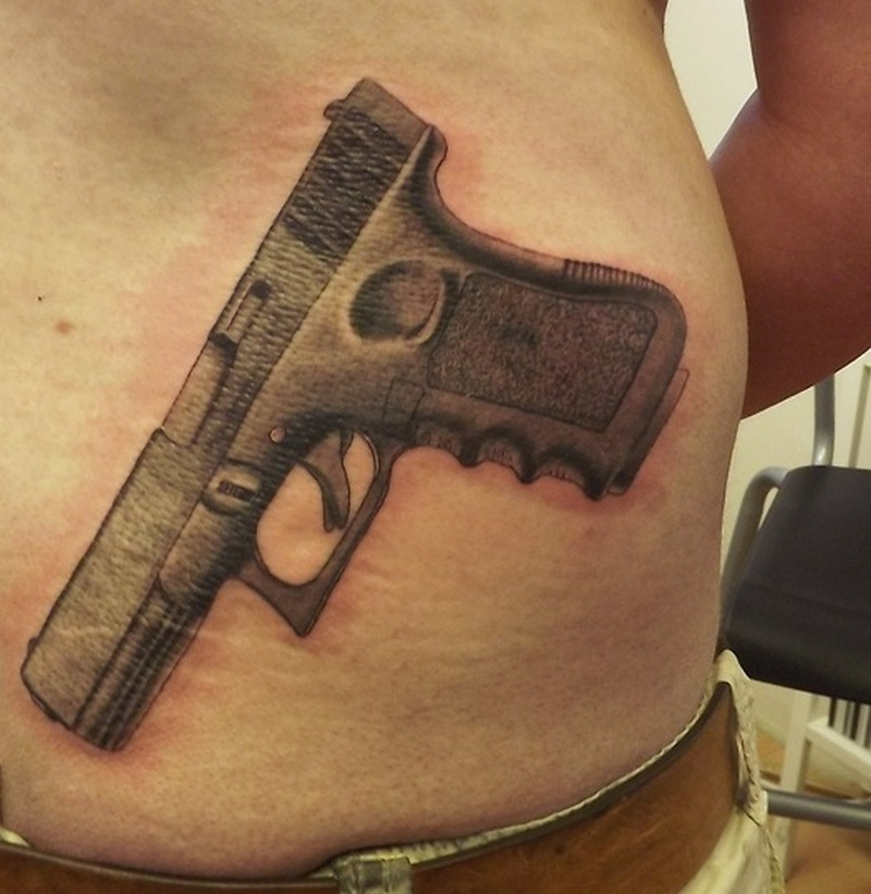 Superb gun tattoo on waist