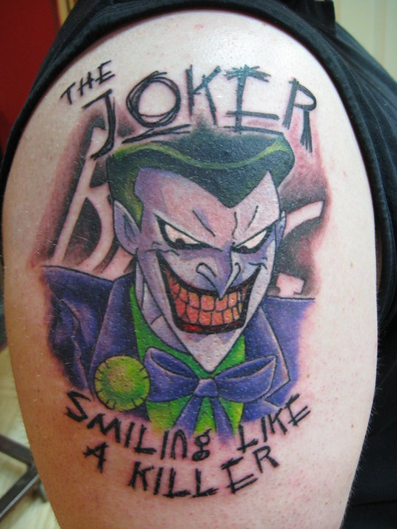 The joker smiling like a killer tattoo on arm