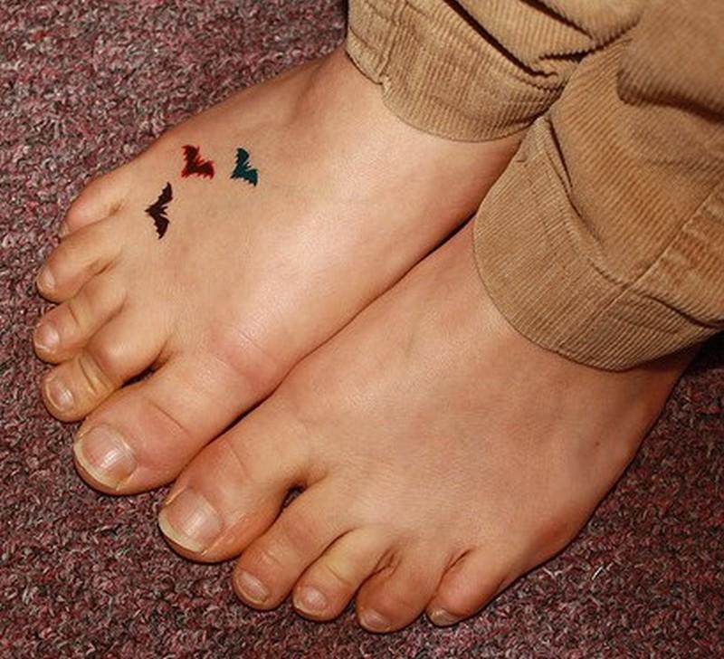 Tiny bats tattoo on foot