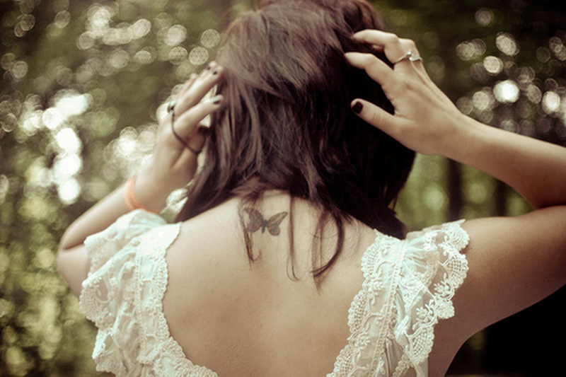 Tiny butterfly tattoo on upper back for girls