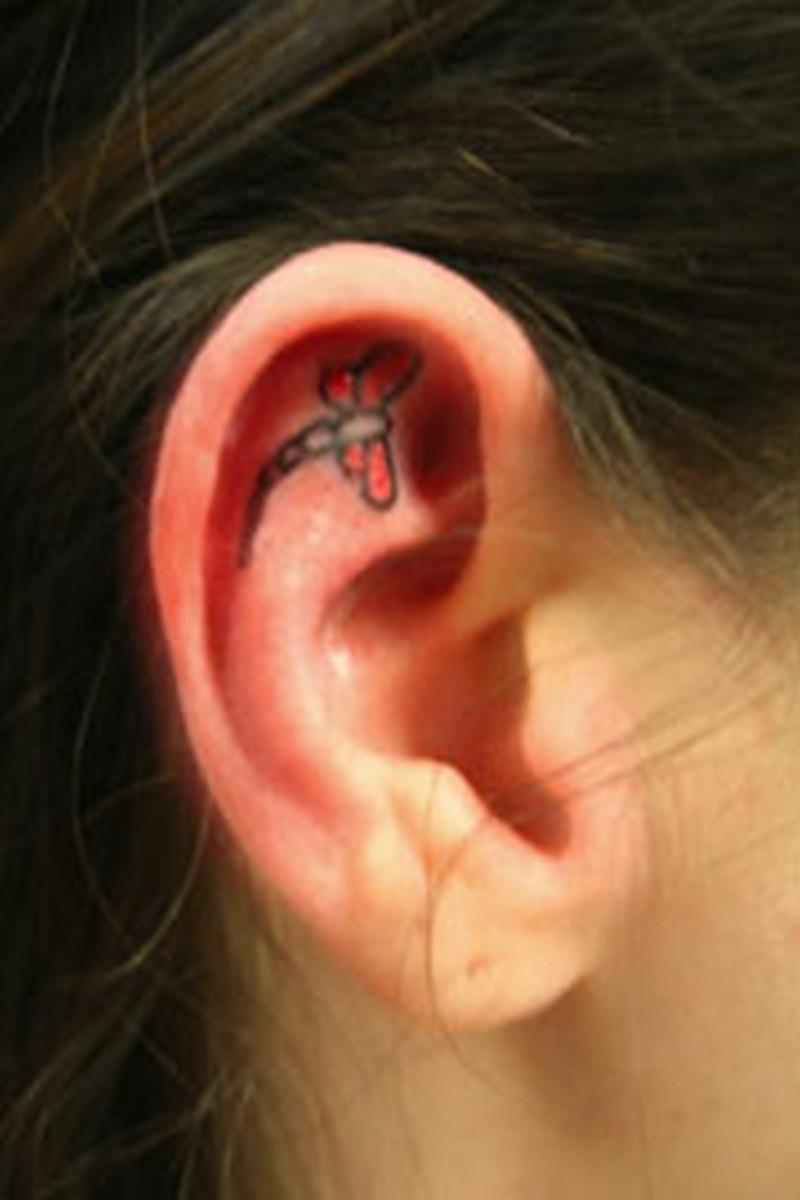 Tiny dragonfly ear tattoo design