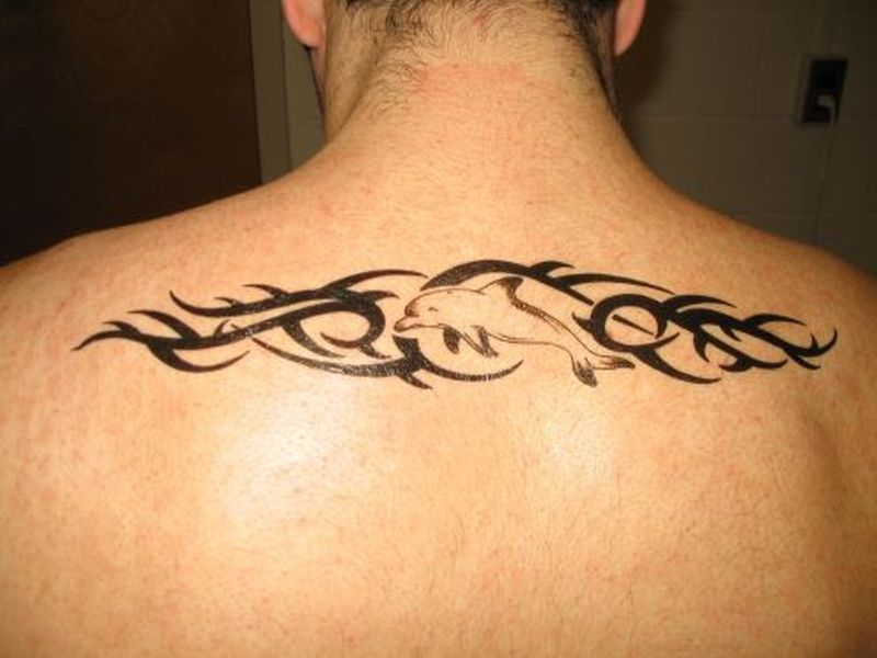 Tribal dolphin picture on upper back tattoo