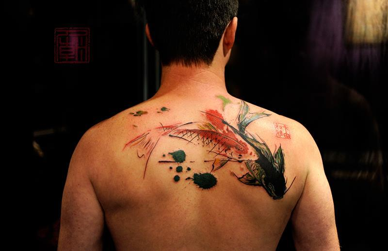 Two koi fish get a modern design style in this artistic abstract tattoo