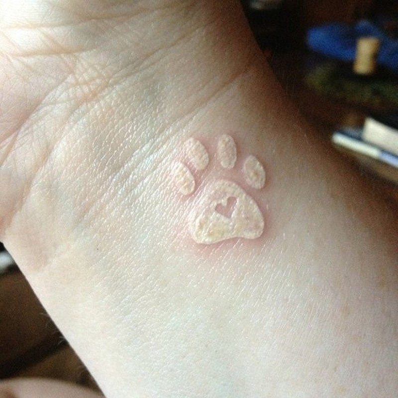 White ink heart in paw print tattoo on wrist - Tattoos Book