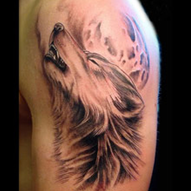 Wolf face tattoo on biceps