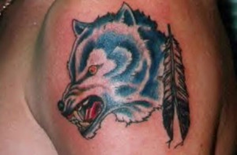 Wolf feather tattoo on biceps