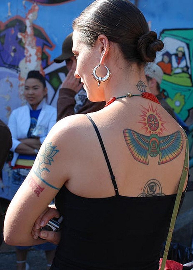 Woman with egyptian on upper back tattoo