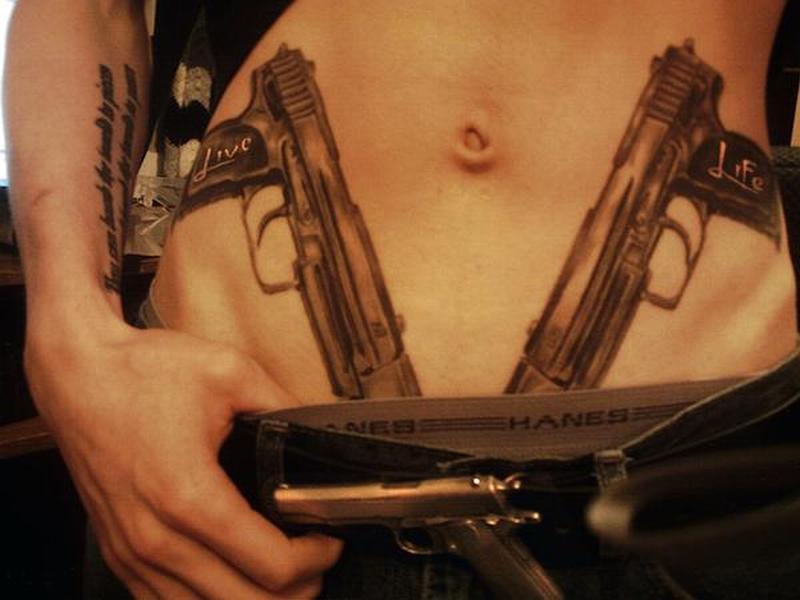 Wonderful gun tattoo design on stomach