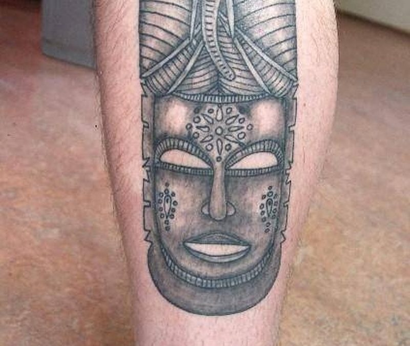 African mask tattoo on leg