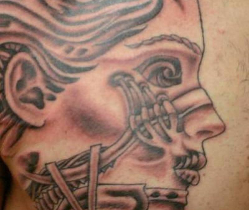 Biomechanical face tattoo design on chest