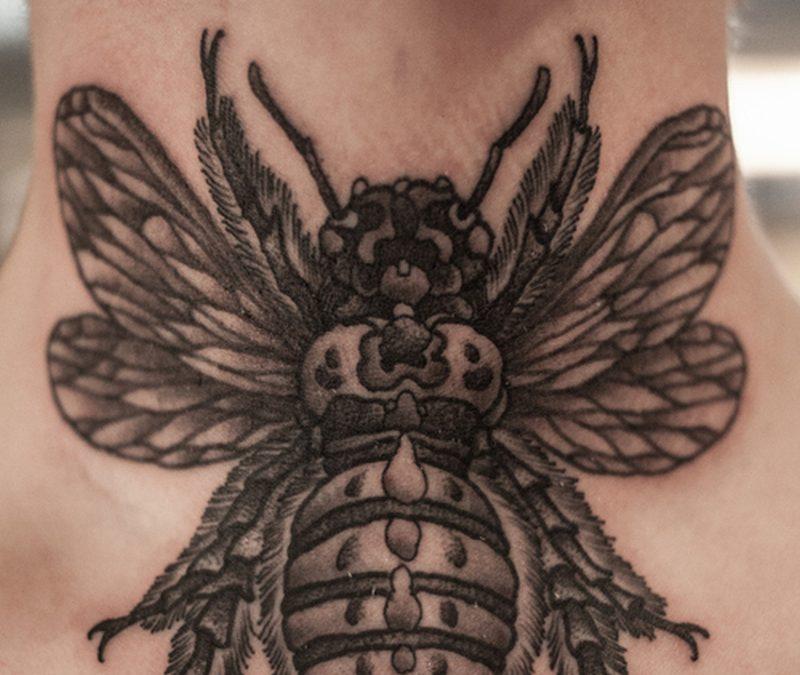 Black bee tattoo on neck
