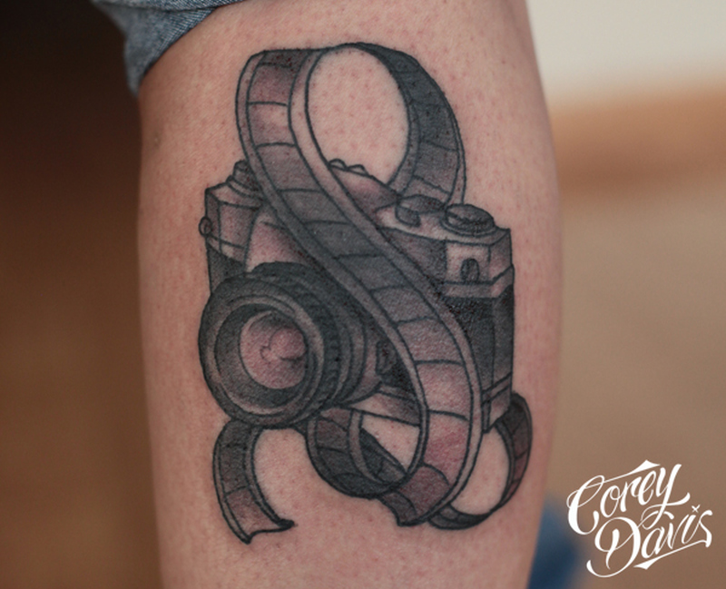 Black ink camera with film tattoo