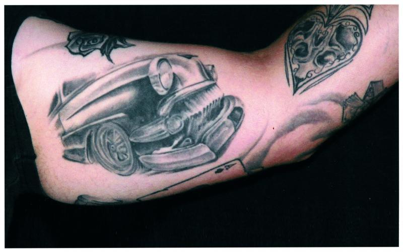 Black ink car front tattoo on muscles