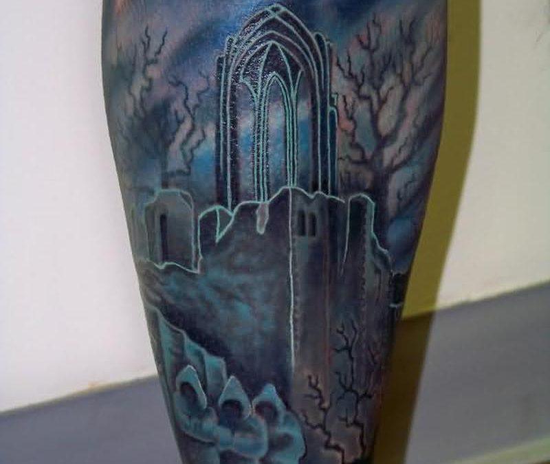 Blue ink graveyard tattoo design on leg