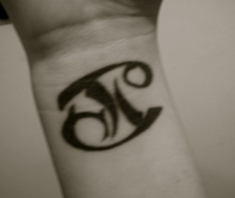 Cancer pisces combined tattoo on wrist