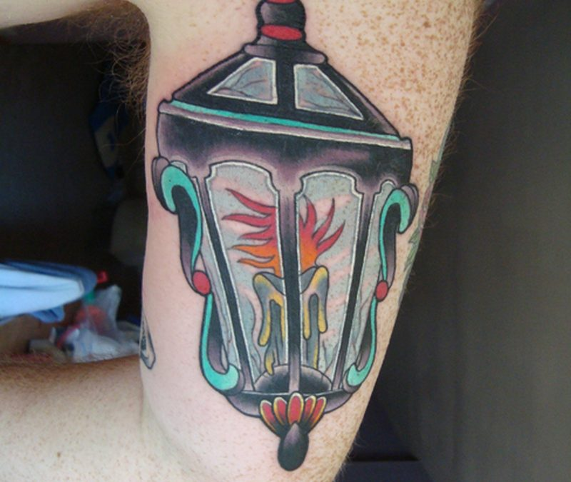 Candle lantern tattoo on muscles