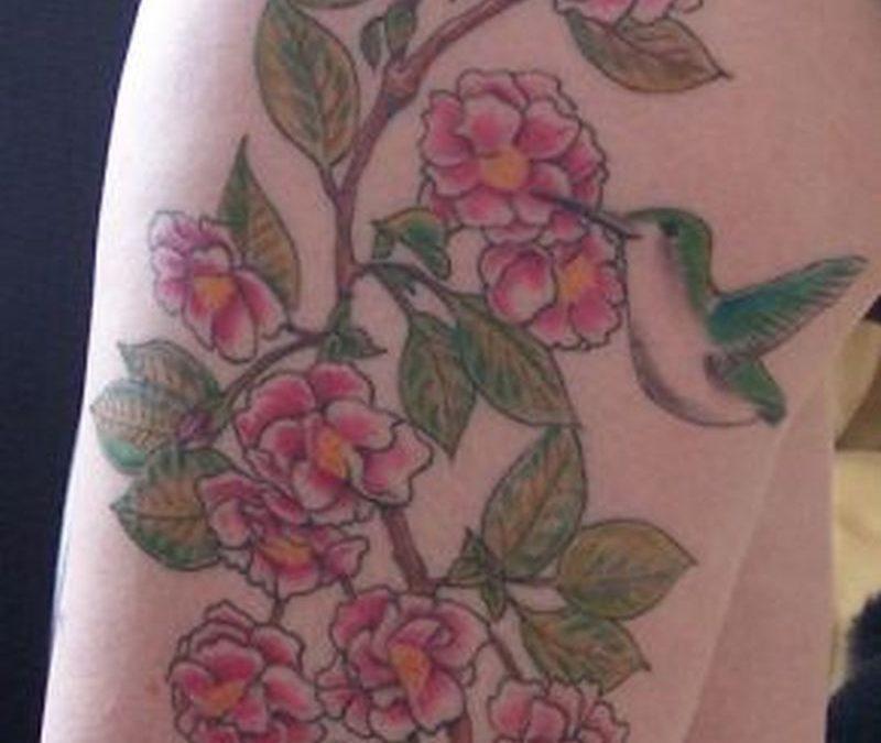 Cherry blossom and hummingbird tattoo on thigh