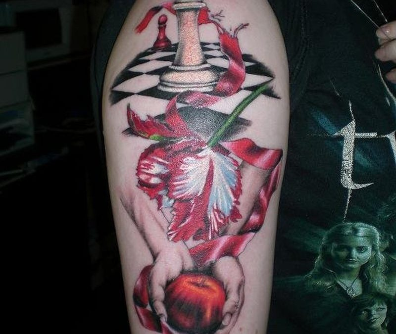 Chess ribbon apple on arm tattoo