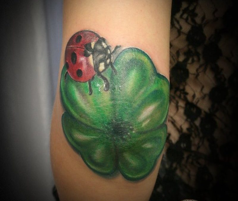 Clover with ladybug tattoo on elbow