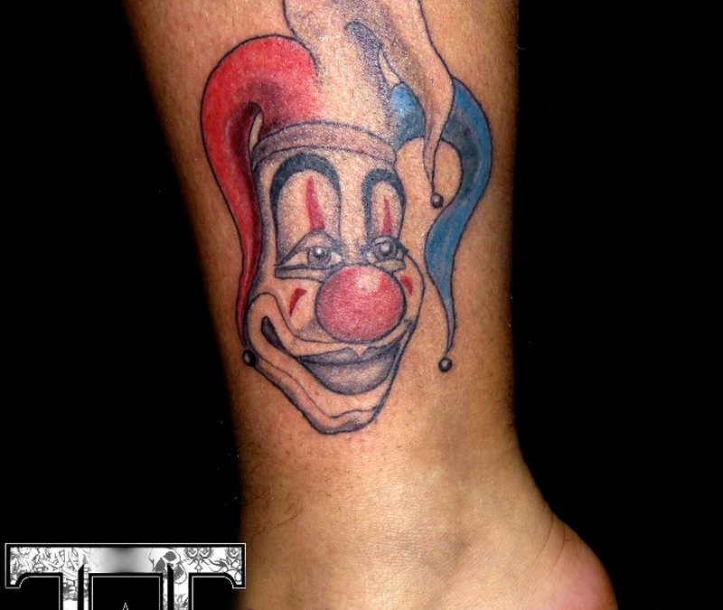 Clown face tattoo on ankle