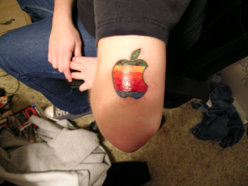 Color ink apple tattoo on thigh