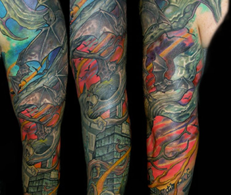 Color ink graveyard tattoo on sleeve