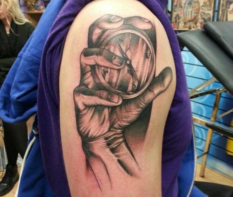 Compass in hand tattoo on shoulder