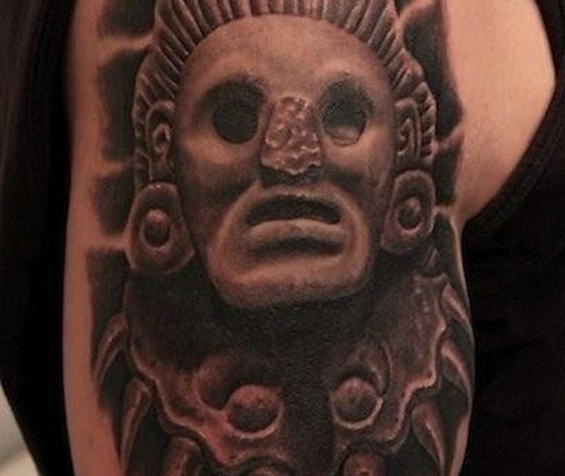 Cool stone head of a pagan deity tattoo on shoulder