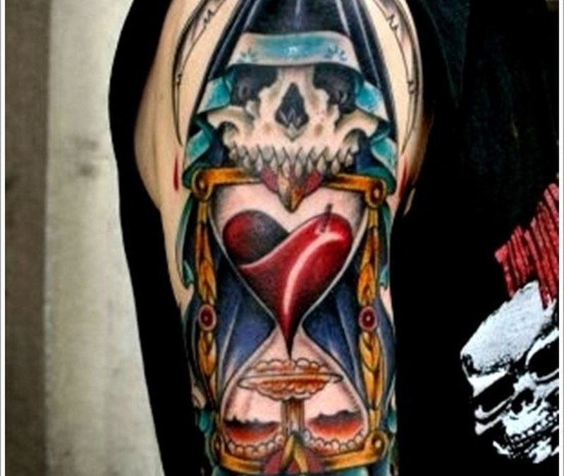 Death with a scythe and hourglass tattoo on shoulder