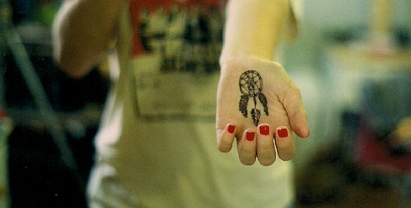 Dream catcher tattoo on palm n red nail polish