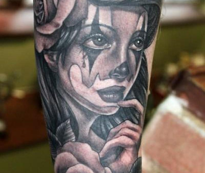 Female clown on arm tattoo