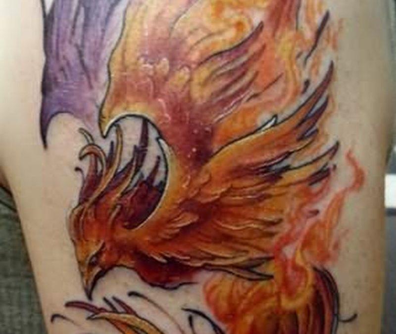 Flaming phoenix bird tattoo on biceps