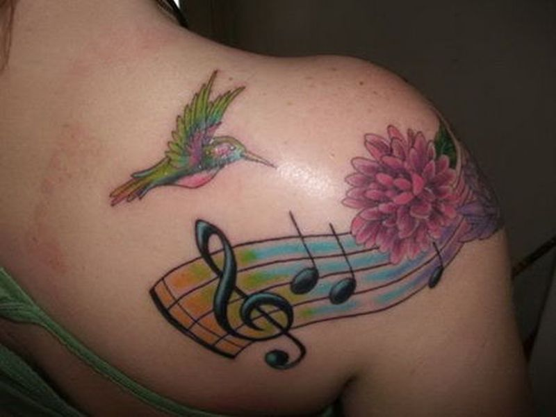 Flying hummingbird with music notes tattoo design