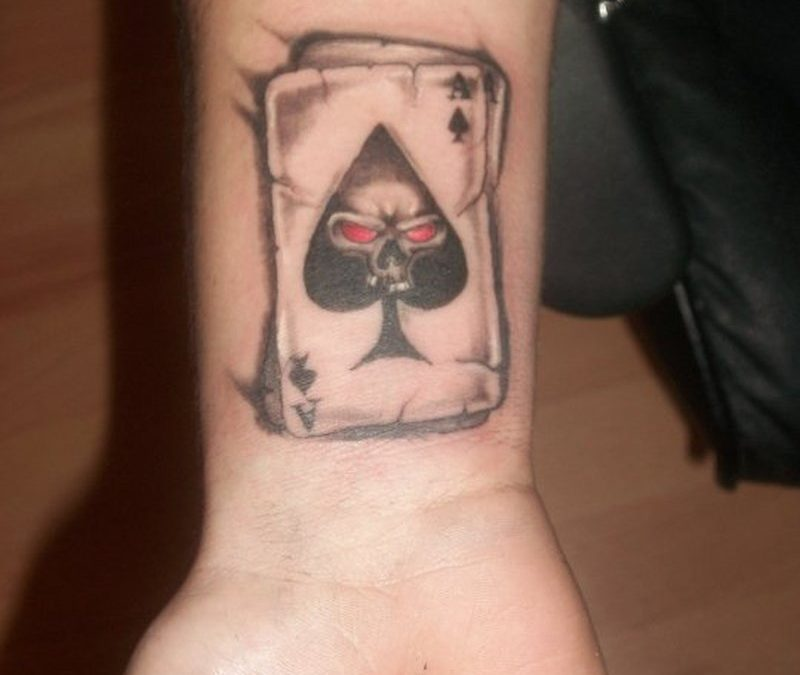 Gambling card with skull tattoo on wrist
