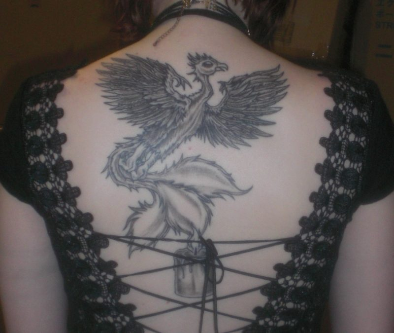 Grey ink phoenix rising candle tattoo on back