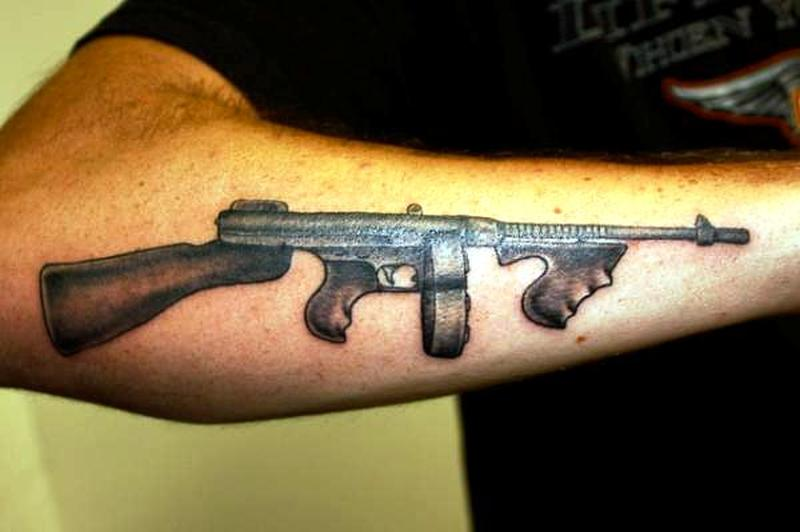 Machine gun design on arm tattoo