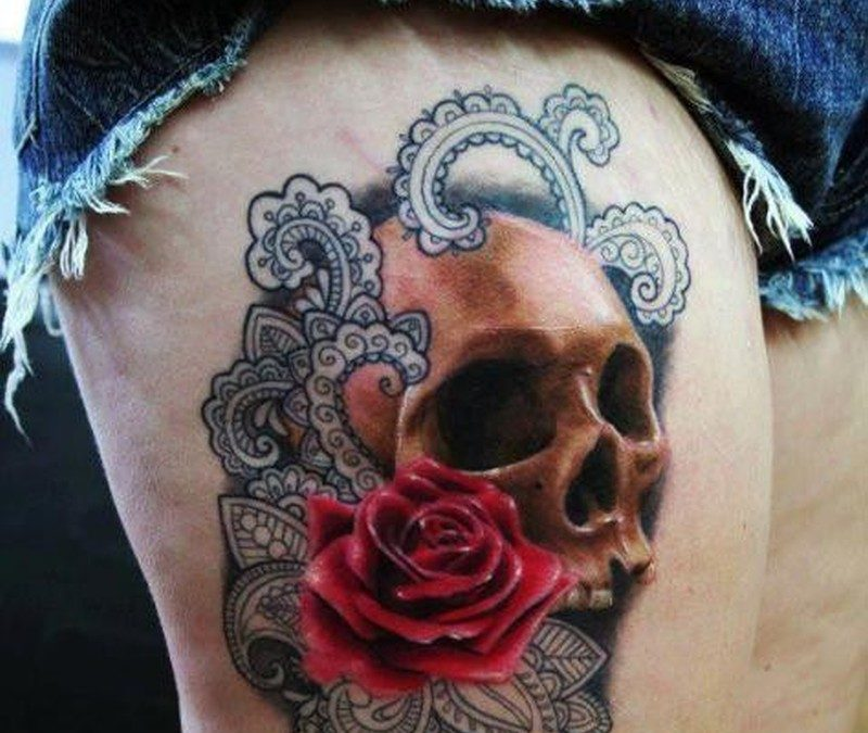 Realistic skull with red rose and black patterns tattoo on thigh for women by Kata Urban