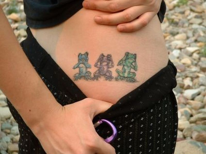 Showing three frogs on upper hip tattoo