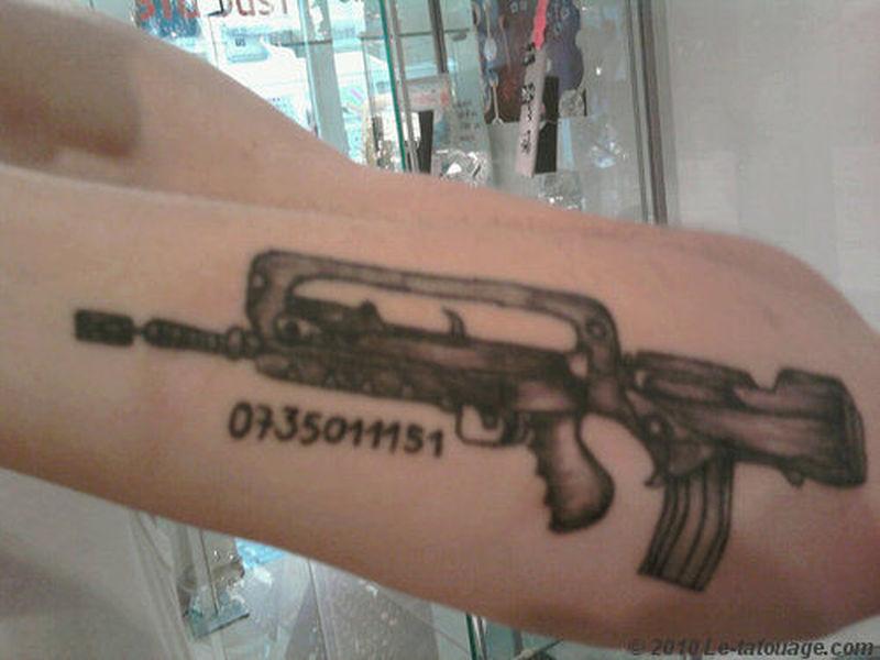 Superb gun tattoo design on arm