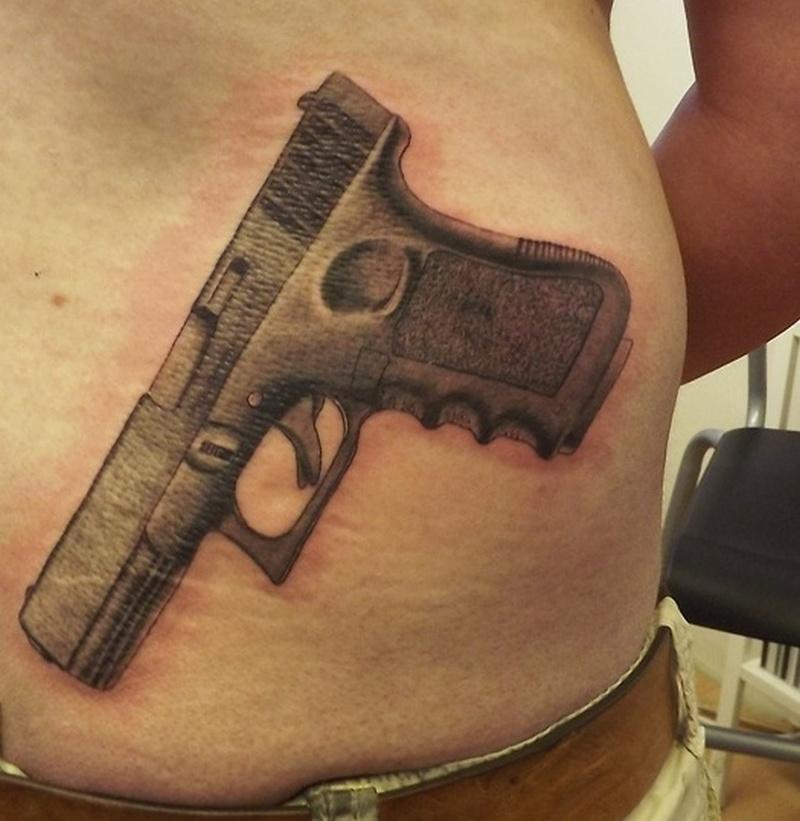 Superb gun tattoo on waist