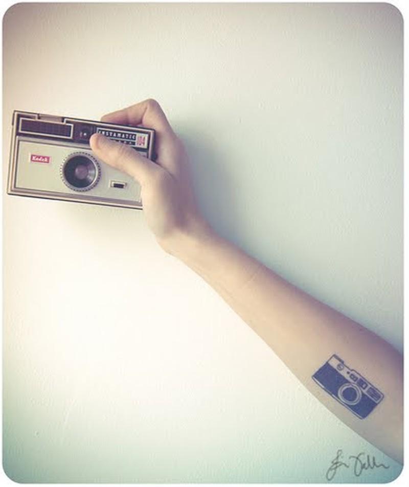 Vintage camera tattoo on arm